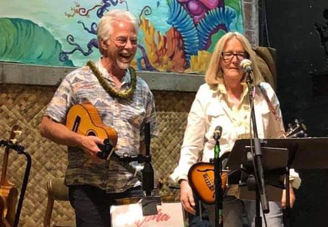 Man and woman playing uke at Pono